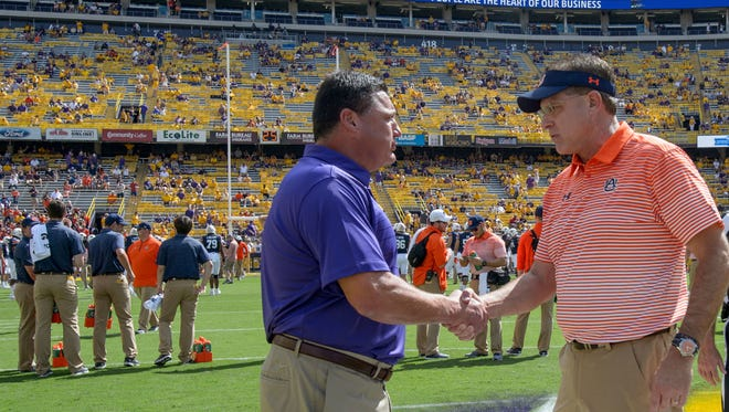 LSU head coach Ed Orgeron, left, greets Auburn head coach Gus Malzahn before an NCAA college football game in Baton Rouge, La., Saturday, Oct. 14, 2017. (AP Photo/Matthew Hinton)