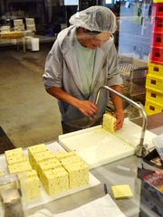 An employee at Springside Cheese cuts a section of pepperjack for packaging.