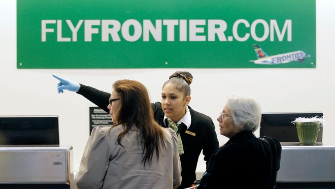 A Frontier Airlines employee wears gloves as she directs passengers where to go at Cleveland Hopkins International Airport Wednesday, Oct. 15, 2014, in Cleveland. Ohio health officials aren't sure how many people came into contact with a Texas nurse as she visited family in the Akron area days before being diagnosed with Ebola in Dallas. The Ohio Department of Health says she visited family from Oct. 8-13 and flew Monday from Cleveland to Dallas.