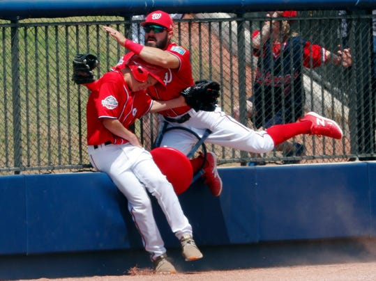 Washington Nationals left fielder Adam Eaton, right, crashes into a ballboy as he catches a foul ball hit by Miami Marlins' Cristhian Adames in the second inning of a spring training baseball game Saturday, March 24, 2018, in West Palm Beach, Fla. (AP Photo/John Bazemore)