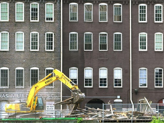 The warehouses on First Avenue set a historic background as demolition crews take down the not-so-historic Fort Nashborough on Friday in preparation of building a new interpretive center as a replacement.