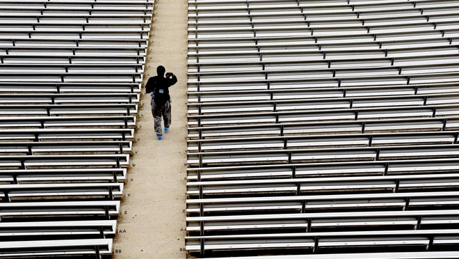 FILE - In this July 16, 2014, file photo, a student walks through empty seats inside Kenan Stadium at the University of North Carolina in Chapel Hill, N.C., where preparations continue for the upcoming college football season. The crippling grip the coronavirus pandemic has had on the sports world has forced universities, leagues and franchises to evaluate how they might someday welcome back fans.