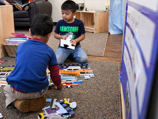 Brothers build a puzzle  in a mixed age group classroom