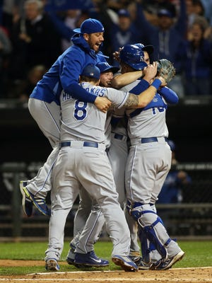 Kansas City Royals players celebrate on the field after clinching a playoff berth.