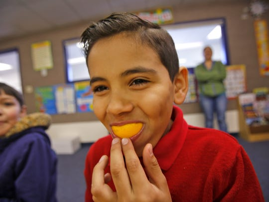 Pablo Montes eats an orange slice Friday at McCormick Elementary School in Farmington as part of the Breakfast After the Bell program.