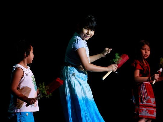 "At center, Akina John, 10, of Shiprock, performs a gourd dance on Friday during the ""Dahayóígíí"" art event at the Phil L. Thomas Performing Arts Center in Shiprock."
