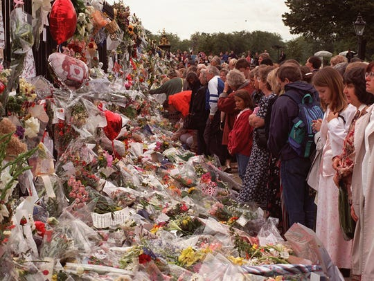 Crowds of people line up to leave flowers at Kensington