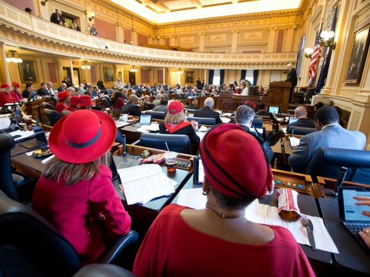 Members of the Virginia House of Delegates, Del. Daun Hester, D-Norfolk, front right, as well as Del. Eileen Filler-Corn, front left, along with other members of the House wear red hats and outfits to commemorate Valentines day during the House session at the Capitol in Richmond, Va., Tuesday, Feb. 14, 2017.