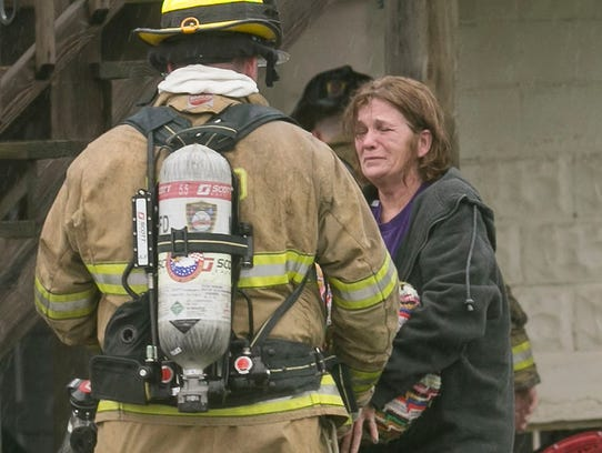 A firefighter talks to a woman at the scene of a house