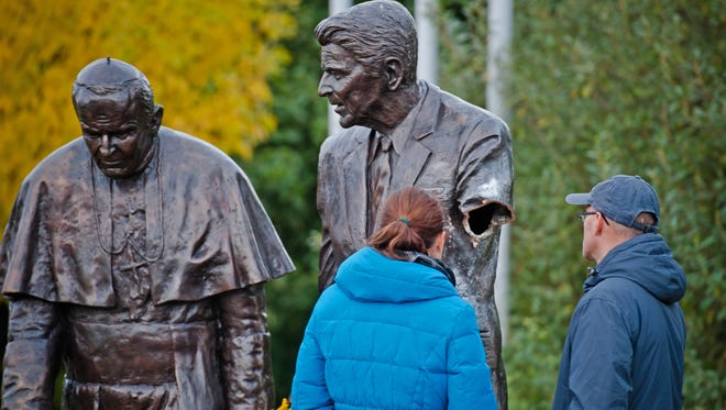 Passersbys are seen looking at a statue of former president Ronald Reagan after the arm was severed in a park in Gdansk, Poland, on Oct. 1.