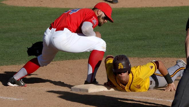 Arizona State's  Andrew Snow dives back to first base under the tag of Arizona's JJ Matjevic during the eighth inning. The Sun Devils defeated the Wildcats 5-1 on Sunday.