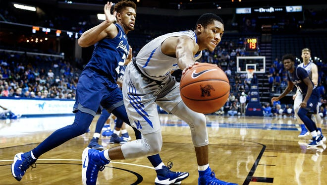 University of Memphis guard Craig Randall II (right) looks to save a ball from going out of bounds while defended by Jackson State University defender Edric Dennis (left) during first-half action at FedExForum.