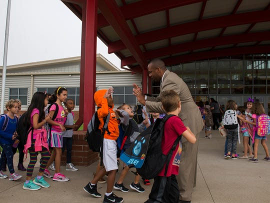 Millard House II, director of schools, high-fives students at Rossview Elementary as they get off the buses before starting school Aug. 29, 2017. Rossview Elementary, which has an enrollment of 906 students and is at 117 percent of the design capacity of the building this school year.