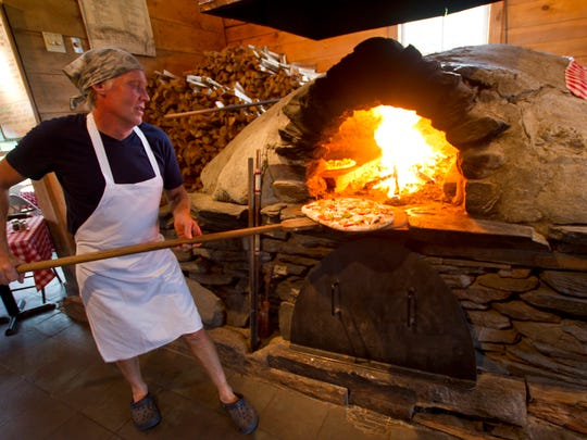 A pizza is put in the wood-fired oven at American Flatbread