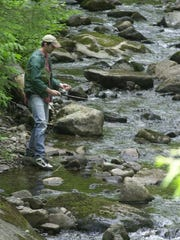 A man fishes in a stream on the Kingdom Heritage Lands.