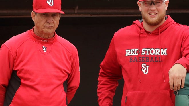 FILE - In this March 25, 2017, file photo, St. John's NCAA college baseball head coach Ed Blankmeyer, left, and pitcher Jeff Belge watch from the dugout during a game against Maine in New York. Blankmeyer went into this season expecting his St. John's baseball team to get off to a solid start. But not even the veteran coach could have predicted the Red Storm to roll quite like this. They're soaring up the national polls at 18-2, their best start since the 1981 squad that featured future major leaguers Frank Viola and John Franco opened 26-1. (AP Photo/Gregory Payan, File)
