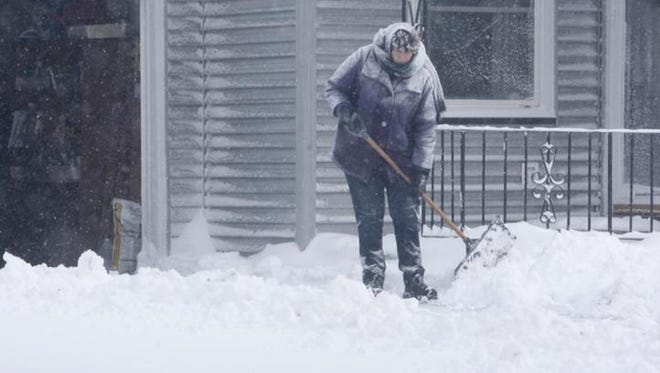 Phyllis Draycott of Batavia shovels her driveway on Tuesday.
