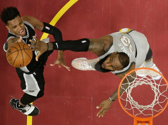 San Antonio Spurs' Dejounte Murray, left, shoots over Cleveland Cavaliers' LeBron James (23) in the first half of an NBA basketball game, Sunday, Feb. 25, 2018, in Cleveland. (AP Photo/Tony Dejak)