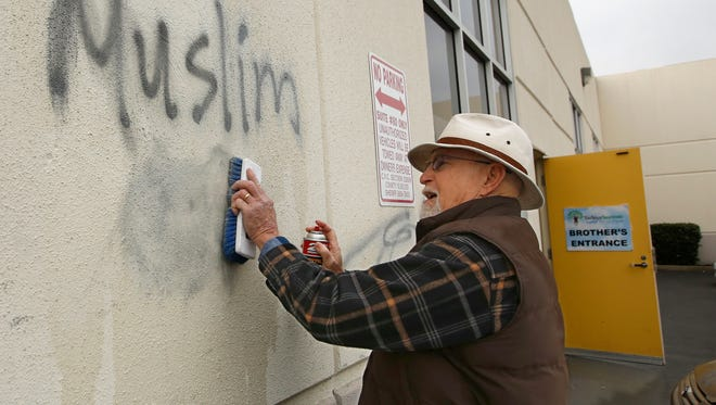 In this Feb. 1, 2017, file photo, Tom Garing cleans up racist graffiti painted on the side of a mosque in what officials called an apparent hate crime, in Roseville, Calif. A report released by the California Attorney General's office, Monday says hate crimes jumped more than 17 percent last year, though they remain relatively rare.