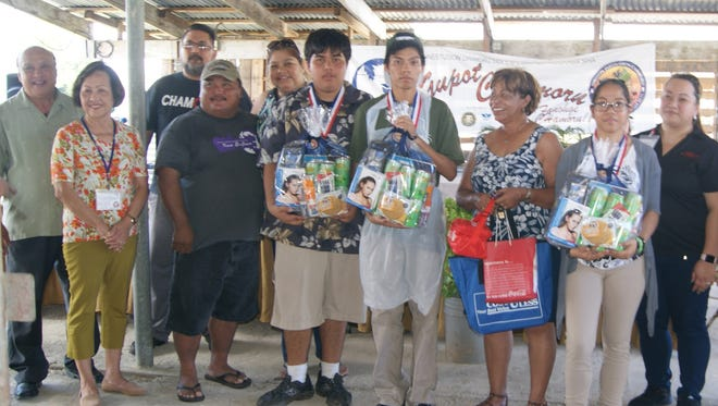 The GDOE Chamoru Studies Division held a Gerran Kadon Pika Competition(Hot & Spicy) on March 11, at Mangilao Night Market, one of several Island-wide Chamoru Month 2017 Activities. Category 3, 1st Place Winner, Tiyan High School  Pictured:  Brandon Respicio, Benjamin Hernandez, and Katarina Hernandez. Pictured from left: Johnny Sablan (Judge), Maria Guiterrez (Judge), Ron Fejeran (Judge), Parent), Monica Fejeran (Parent), Matilda Iwanaga (Adult Representative/Teacher), Queenie Ayuyu (Judge), Sinot Jimmy Teria (Chamoru Studies & Special Projects Division, School Program Consultant), and Sinora Rufina Mendiola(Chamoru Studies & Special Projects Division, Administrator).