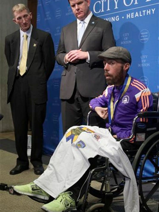 Boston Police Commissioner William Evans, left, and Mayor Marty Walsh, center, listen as Maickel Melamed, of Venezuela, speaks during a ceremony to honor him as the last participant to finish this year's Boston Marathon Tuesday, April 21, 2015, in Boston. Melamed, 39, has a form of muscular dystrophy which severely impairs his mobility. He crossed the finish line about 20 hours after he started.