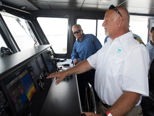 Capt. George Aswad, right, takes the helm of the Pelican