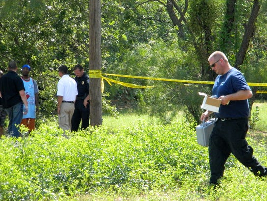 Police investigate a homicide in an alley near the