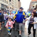 A woman greets Paul Norden, right, as he and his brother, J.P. Norden, left, walk with a group of family and friends down Boylston Street toward the Boston Marathon finish line in Boston, Tuesday, April 15, 2014. The brothers, each of whom lost his right leg in the 2013 Marathon bombings, traveled the 26.2 miles of the marathon route Tuesday as a fundraiser. They face a lifetime of expenses for the prostheses that have replaced their legs.