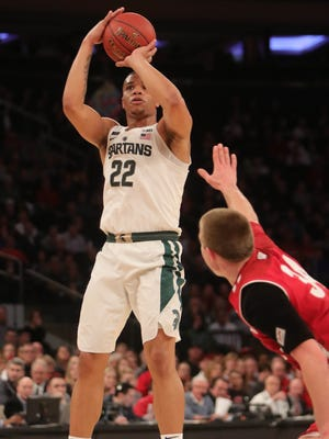 Michigan State guard Miles Bridges scores against Wisconsin guard Brad Davison during second half action Friday, March 2, 2018 at Madison Square Garden in New York.