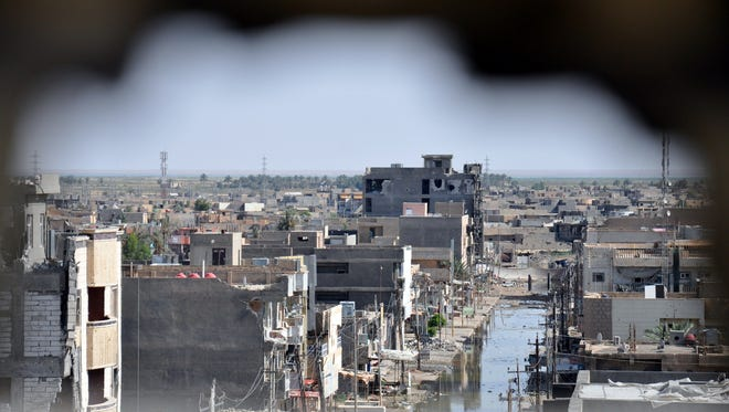 Photographed through a hole in a wall on June 24, 2014, buildings in Ramadi, Iraq, show the damage caused during recent violence.