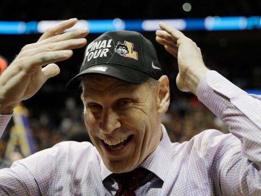 Loyola-Chicago head coach Porter Moser puts on a cap after a regional final NCAA college basketball tournament game against Kansas State, Saturday, March 24, 2018, in Atlanta. Loyola-Chicago won 78-62. (AP Photo/David Goldman)