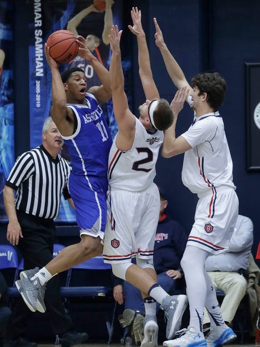 UNC-Asheville guard Jalen Seegars (11) is defended by Saint Mary's (Cal.) forward Calvin Hermanson, center, and center Jordan Hunter during the first half of an NCAA college basketball game in Moraga, Calif., Friday, Dec. 22, 2017. (AP Photo/Jeff Chiu)