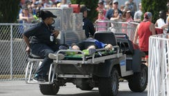 EMTs cart a runner off to get medical attention at