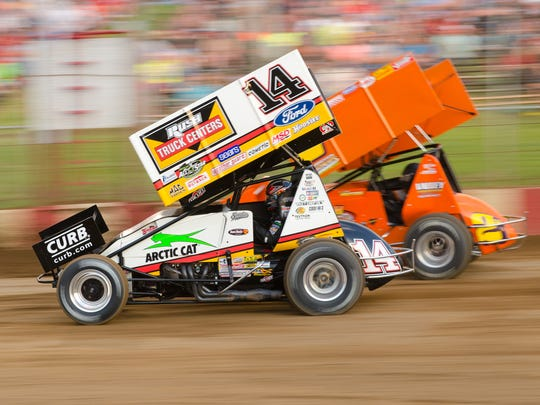 Three-time NASCAR champion Tony Stewart (14) passes local driver Scott Neitzel en route to a heat race victory at Angell Park Speedway in 2017.