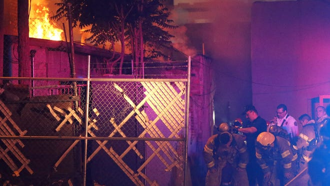 Firefighters are outfitted with air packs as a fire rages at left along South El Paso Street one block South of Paisano Drive Monday night.