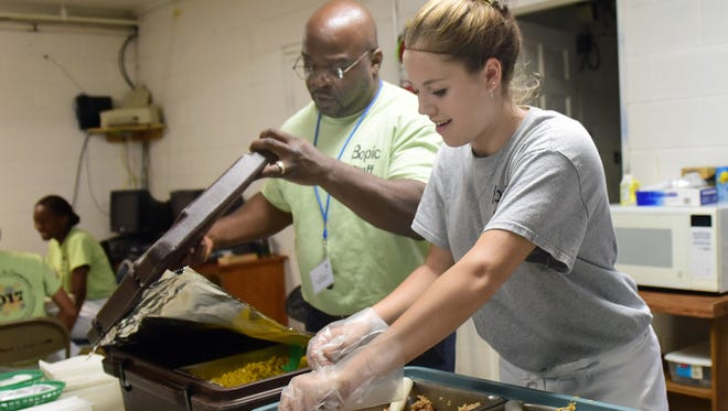 Antonio Harrison helps Jazlyn Moquin, 15, prepare meals during the BOPIC Youth Leadership program Tuesday, June 27, 2017 at John Wesley AME Church, Chambersburg. Harrison is the director of youth outreach coordinator.