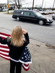 A woman holds an American flag as the hearse carrying