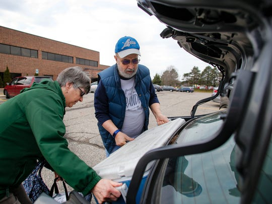 Meals-on-Wheels volunteers Wes and Gladys Thorp of Lansing load up their trunk with a cooler of freshly prepared food they'll deliver to shut-ins and the elderly Friday, March 24, 2017, at the Tri-County Office on Aging.