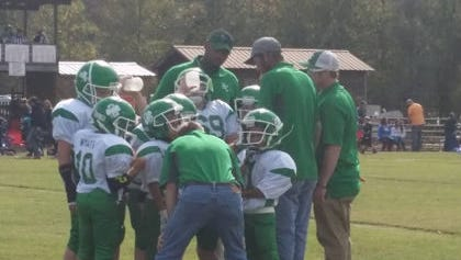 The Fighting Irish Jr. Pro minor team huddles up during their game against the Waverly Tigers on Nov. 5, 2016. They won and advance to the Super Bowl.