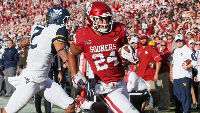 Oklahoma running back Rodney Anderson (24) scores in front of West Virginia safety Kenny Robinson (2) in the first quarter of an NCAA college football game in Norman, Okla., Saturday, Nov. 25, 2017. (AP Photo/Sue Ogrocki)