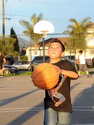 Edwin Perez, 6, is determined to score a basket. On his fifteenth try, he sunk this shot at Closter Park in east Salinas.