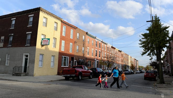 The former site of the John T. Lewis-National Lead-Anzon factory is surrounded by a row houses like these, shown in a 2012 file photo. Many of the homes have backyards where children play.