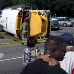 Spectators, many of them parents concerned their child might be on this overturned bus, look over the scene of the accident between at Escambia County school bus and a dump truck Thursday afternoon at the intersection of Pace Boulevard and Jordan Street.