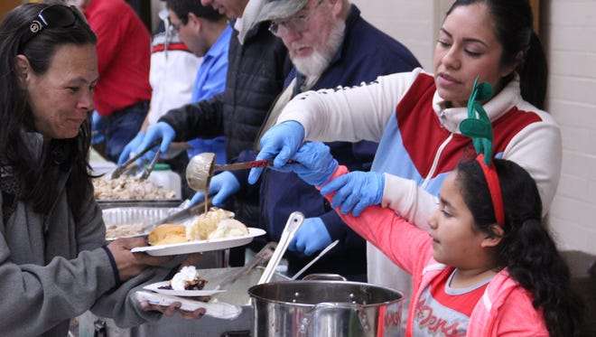 Delilah Avila, 7, and her mother Paloma Hernandez serve gravy to Liz Barnhart, of Marina, at the Sacred Heart Church's Community Christmas Dinner Monday afternoon in Salinas. Volunteers estimated they'd serve 500 meals before the end of the event, which was free and open to the public. Santa Claus also stopped by to deliver presents.