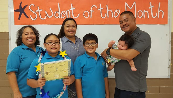 The Guahan Academy Charter School honored its September Student of the Month awardees on Oct.12. Pictured from left (front row): Ciana'lyn Sablan-Cruz; Kenapu Sablan-Cruz and Kenneth Cruz with his baby Kenoa Sablan-Cruz. Pictured from left (back row): Mary Mafnas, Dean of Elementary School Guahan Academy Charter School and Josett Cruz