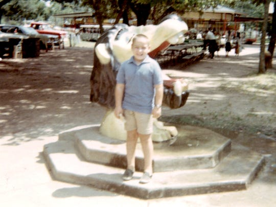 A child is shown in front of a popular lion water fountain located at the Alexandria Zoo during the late 1960's