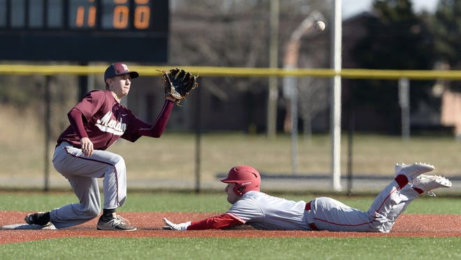Pittsford Mendon's Zachary Janson, left, waits for the throw as Canandaigua's Seth Vigneri slides safely into second base during the first game of a double header played at Monroe Community College, Saturday, April 21, 2018. Canandaigua beat Pittsford Mendon in the first game 14-4.