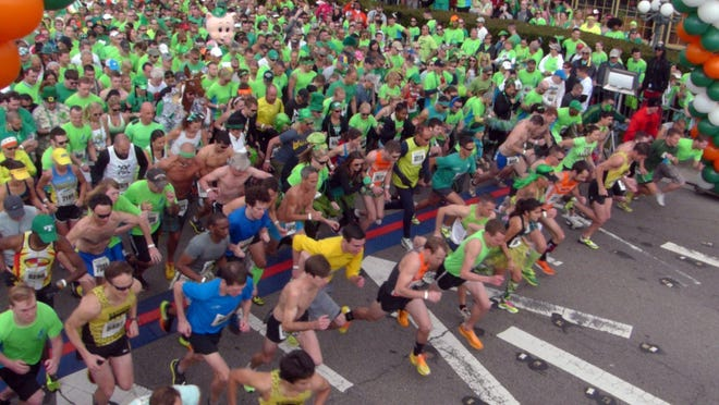 Thousands of runners take off from the starting line of the McGuire's St. Patrick's Day 5K Prediction Run.