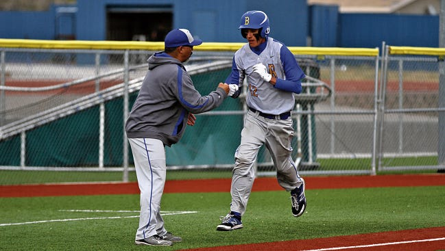 Bloomfield Coach Frank DeHoyos congratulates Brendon Charley as he rounds third base after hitting a solo home run against Shiprock in a game on April 16, 2015, at John Gutierrez Stadium in Bloomfield.