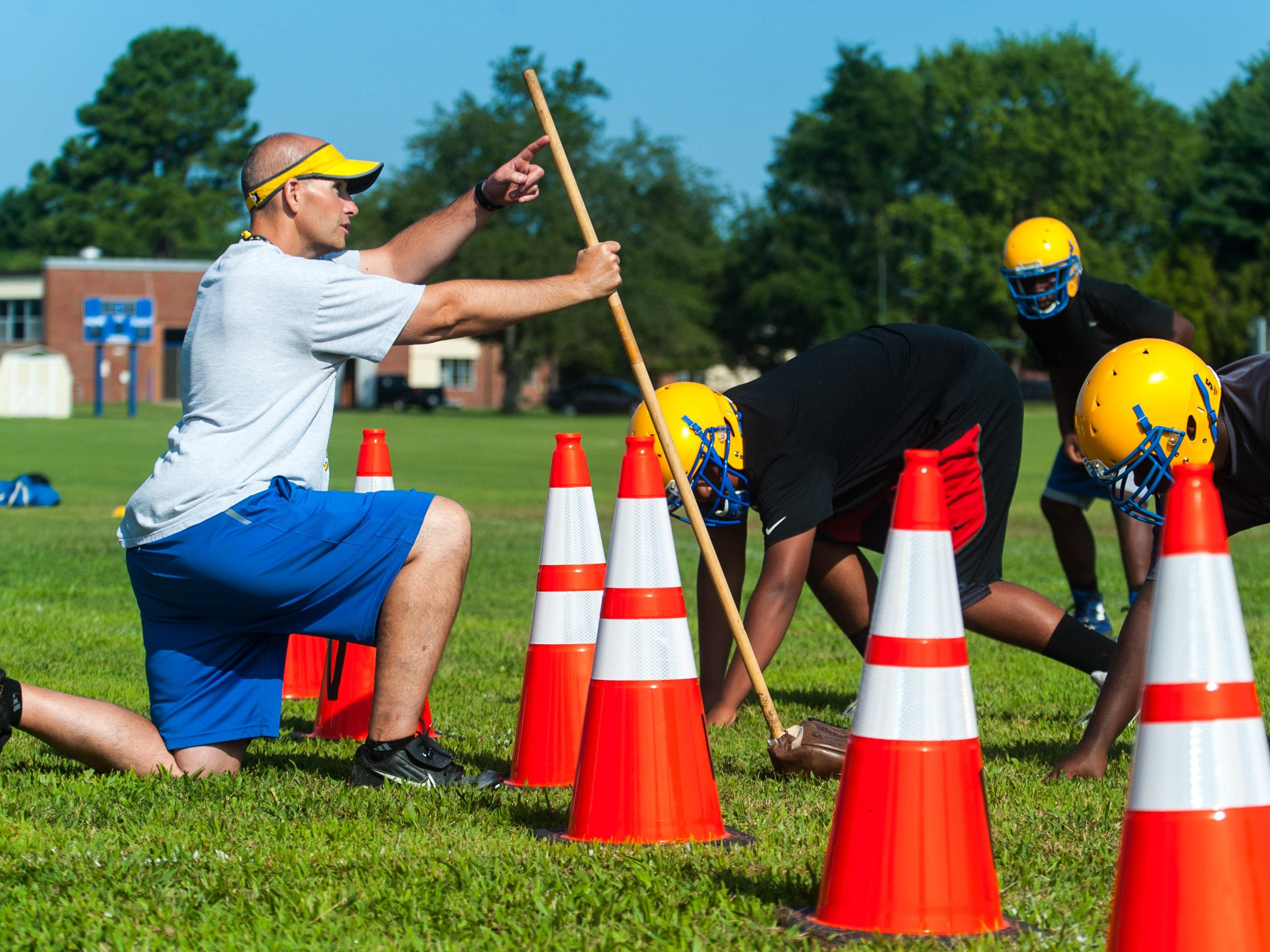 Wicomico High head coach Patrick McGlinchey works with his offensive line on the second day of practice.